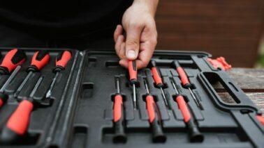 maintenance | hand picking up a screwdriver