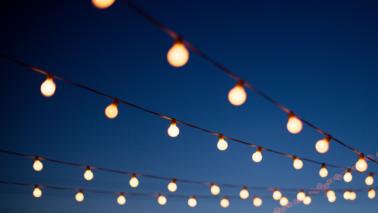 outdoor lights strung up under an evening sky