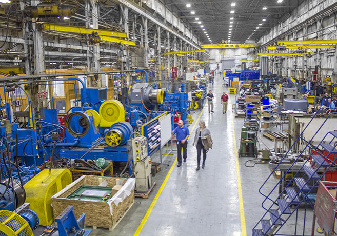 people walking through a press part manufacturing facility
